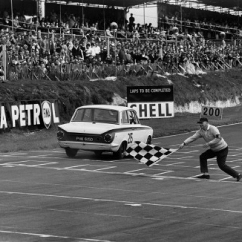 1966 Brands Hatch, England. August 1966. Jim Clark, Lotus Cortina, 1st position, takes the chequered flag.jpg